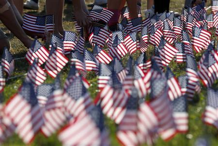 People plant some of the 3000 U.S. flags placed in memory of the lives lost in the September 11, 2001 attacks, at a park in Winnetka, Illinois, September 10, 2013. REUTERS/Jim Young