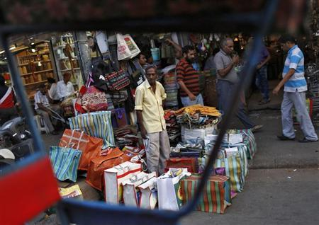 A vendor waits for customers, at his roadside stall selling bags, at a wholesale grocery market in the old quarters of Delhi June 13, 2013. REUTERS/Ahmad Masood