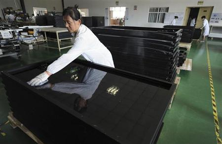 An employee cleans newly produced solar panels at a solar power plant in Hefei, Anhui province July 26, 2012. REUTERS/Stringer