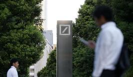 Men walk past a logo of Deutsche Bank AG in Tokyo September 9, 2013. REUTERS/Toru Hanai