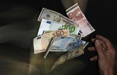 Банкноты евро и доллара США в Праге 23 января 2013 года. Рубль подрос к евро и корзине валют, стабилен в паре с долларом США при открытии биржевой сессии среды, дальнейшая динамика будет зависеть от денежных потоков перед очередным налоговым периодом, пятничным советом директоров ЦБР и заседанием ФРС США на следующей неделе. REUTERS/David W Cerny