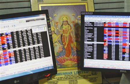 An image of Lakshmi, the Hindu goddess of wealth and prosperity, is placed between monitors displaying share price index at a share trading market in the northern Indian city of Chandigarh August 29, 2013. REUTERS/Ajay Verma