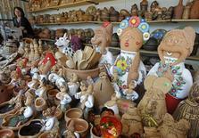 Женщина продает гончарные изделия в поселке Опошня Полтавской области 24 мая 2011 года. Правительство Украины одобрило в среду проект бюджета на 2014 год, рассчитанный исходя из ожиданий роста ВВП на 3,0 процента и инфляции на уровне 8,0 процента, сообщила советник президента страны по экономике Ирина Акимова. REUTERS/Gleb Garanich