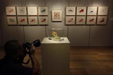 Fotógrafo registra peça feita por Andy Warhol exposta na galeria de Hong Kong da casa de leilões Sotheby's. Mais de 40 obras do artista pop Andy Warhol serão exibidas numa exposição promovida pela casa de leilões Sotheby's em Hong Kong, sendo a mais cara delas avaliada em cerca de 1 milhão de dólares. 11/09/2013. REUTERS/Bobby Yip
