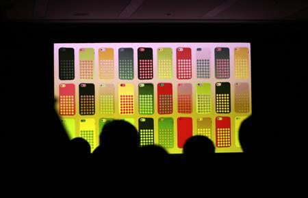 Journalists watch a screen showing the new iPhone 5C in different colours at Apple Inc's announcement event in Beijing, September 11, 2013. REUTERS/Jason Lee