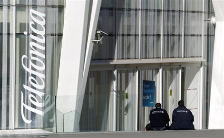 Workers rest sitting next to Telefonica's tower entrance in Barcelona January 30, 2013. REUTERS/Albert Gea