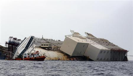 The capsized cruise liner Costa Concordia lies surrounded by containers called ''sponsons'' as part of the salvage plan to remove the wreck of the ship outside Giglio harbour August 8, 2013. REUTERS/Stefano Rellandini
