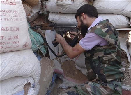 A Free Syrian Army fighter aims his weapon behind sandbags in the eastern al-Ghouta, near Damascus, September 9, 2013. Picture taken September 9, 2013. REUTERS/Raje Alsori