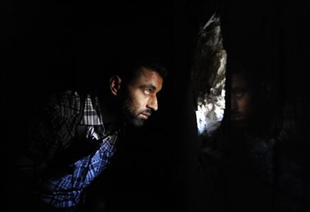 A Free Syrian Army fighter peeks through a hole in a wall in Aleppo's Qastal al-Harami neighbourhood September 11, 2013. REUTERS/Nour Kelze