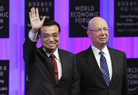 Chinese Premier Li Keqiang (L) waves to the audience next to World Economic Forum founder and executive chairman Klaus Schwab during the opening ceremony of the Annual Meeting of the New Champions 2013, or Summer Davos, in Dalian, Liaoning province, September 11, 2013. REUTERS/China Daily