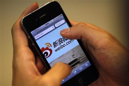 A man holds an iPhone as he visits Sina's Weibo microblogging site in Shanghai in this May 29, 2012 file photo. REUTERS/Carlos Barria/Files