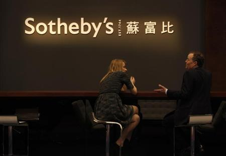 Staff members chat during Sotheby's preview in Hong Kong April 2, 2013. REUTERS/Bobby Yip