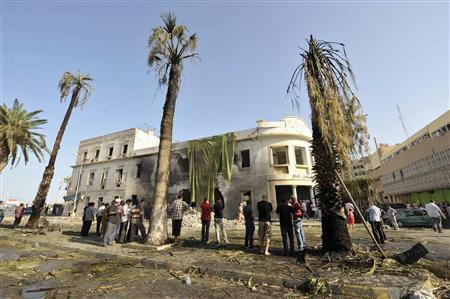 People stand near a Libyan Foreign Ministry building in Benghazi after an explosion in Benghazi September 11, 2013. REUTERS/Esam Omran Al-Fetori