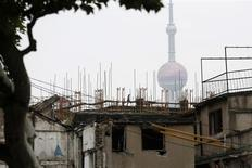 Construction workers work on the scaffolding of a new building in front of the Oriental Pearl TV Tower in an area where old residential buildings are being demolished to make room for new skyscrapers in Shanghai September 9, 2013. REUTERS//Aly Song