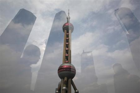 The Oriental Pearl Tower is pictured through a glass wall as people walking past and the skyline behind are reflected on the wall in the financial district of Pudong in Shanghai November 22, 2011. REUTERS/Aly Song