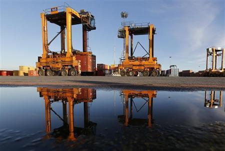 Container cranes are seen reflected in water at Italy's biggest port Gioia Tauro in the southern Italian region of Calabria, November 8, 2012.REUTERS/Alessandro Bianchi