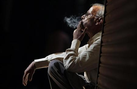A daily wage labourer smokes as he waits for an employer in the old quarters of Delhi, April 29, 2010. REUTERS/Adnan Abidi