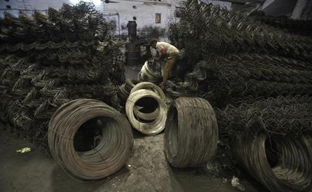 A labourer work inside an iron wire manufacturing factory on the outskirts of Jammu October 9, 2012. REUTERS/Mukesh Gupta/Files