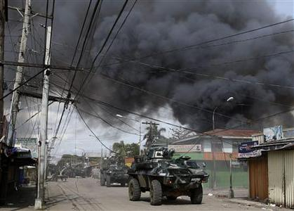 Government soldiers inside armoured vehicles take part in a firefight with Muslim rebels from Moro National Liberation Front (MNLF) amidst smoke from burning houses in a residential district in Zamboanga city in southern Philippines September 12, 2013. REUTERS-Erik De Castro