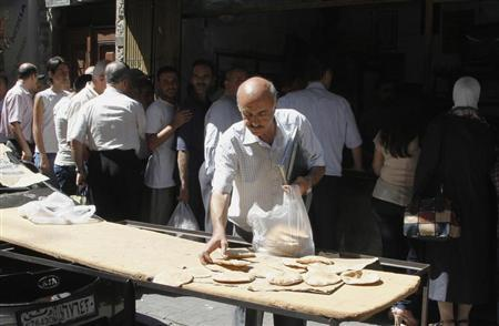 Syrians wait in line to buy bread at al-Shaalan market in Damascus August 28, 2013. REUTERS/ Khaled al-Hariri