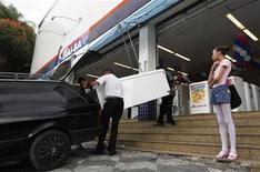 Vendedores carregam geladeira comprada em loja da rede Casas Bahia, em São Paulo. As vendas no varejo brasileiro aceleraram com força em julho ao registrarem crescimento de 1,9 por cento na comparação com o mês anterior, atingindo o ritmo mais rápido desde janeiro de 2012. 18/02/2013. REUTERS/ Nacho Doce