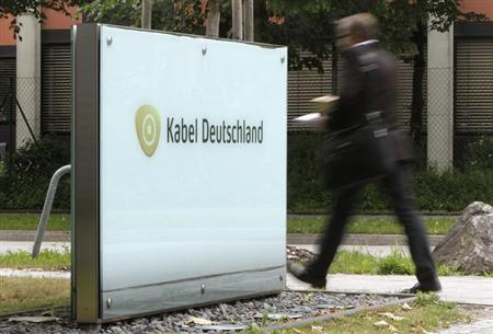A man passes the company logo of German cable television group Kabel Deutschland in Unterfoehring north of Munich June 24, 2013. REUTERS/Michaela Rehle