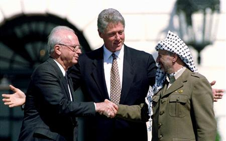 Then U.S. President Bill Clinton gestures as then Israeli Prime Minister Yitzhak Rabin (L) and then PLO Chairman Yasser Arafat shake hands after signing the Israeli-PLO peace accord, at the White House, in this September 13, 1993 file picture. REUTERS/Gary Hershorn/Files