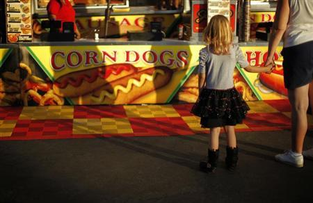 A girl looks at a food stand at the Los Angeles County Fair in Pomona, California September 4, 2013. REUTERS/Lucy Nicholson