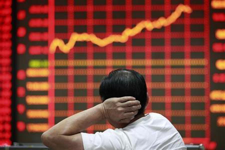An investor looks at an electronic board showing stock information at a brokerage house in Huaibei, Anhui province September 9, 2013. REUTERS/Stringer