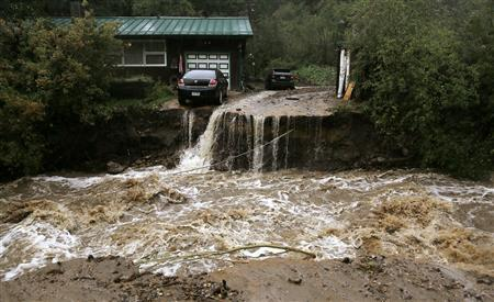 A home and car are stranded after a flash flood in Coal Creek destroyed the bridge near Golden, Colorado September 12, 2013. REUTERS/Rick Wilking