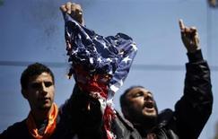 """Палестинцы сжигают американский флаг в Газе 20 марта 2013 года. Лидер исламистской группировки """"аль-Каида"""" Айман аль-Завахри призвал к проведению небольших нападений на территории Соединенных Штатов с целью """"экономически обескровить Америку"""", сообщила мониторинговая служба SITE. REUTERS/Mohammed Salem"""