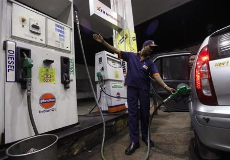 A worker fills a car with petrol as he gestures towards the fuel barometer for the passenger to check, at a fuel station in Kolkata September 15, 2011. REUTERS/Rupak De Chowdhuri/Files