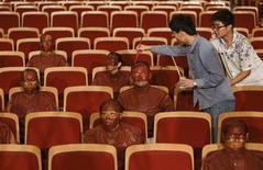 """Artista Liu Bolin é pintado por um assistente, como parte de um projeto para fazer com que ele e outros paticipantes se pareçam exatamente como os assentos de um teatro, em Pequim. O artista chinês, conhecido como """"homem invisível"""" por se camuflar no cenário de fotos usando tintas, fez seu truque novamente, """"sumindo"""" com outras 22 pessoas nas poltronas vermelhas de um teatro de Pequim. Liu diz que a invisibilidade é uma metáfora do drama das pessoas comuns na sociedade moderna. 12/09/2013. REUTERS/Jason Lee"""