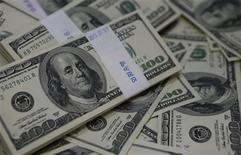 El dólar se debilitó contra el euro y el yen, ya que los inversores ajustaron sus posiciones con miras al fin de semana y a la reunión de política monetaria de la Reserva Federal de Estados Unidos la semana próxima. En la foto de archivo, fajos de billetes de 100 dólares en un banco en Corea del Sur. Ago 2, 2013. REUTERS/Kim Hong-Ji