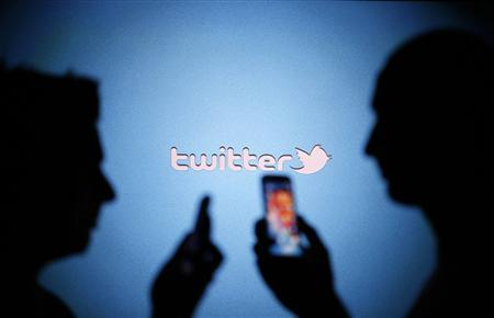 Men are silhouetted against a video screen with a Twitter logo as they pose with Samsung S3 and S4 smartphones in this photo illustration taken in the central Bosnian town of Zenica on August 14, 2013. REUTERS/Dado Ruvic/Files