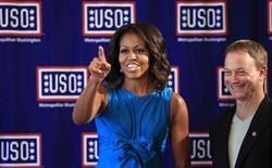 U.S. first lady Michelle Obama points while standing beside actor Gary Sinise during a visit to the newly opened USO Warrior and Family Center at Fort Belvoir, Virginia September 11, 2013. REUTERS/Kevin Lamarque