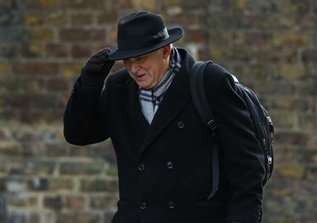 Britain's Business Secretary Vince Cable holds on to his hat as he arrives to attend a Cabinet meeting at Number 10 Downing Street in London March 12, 2013. REUTERS/Andrew Winning