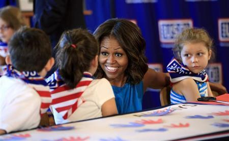 U.S. first lady Michelle Obama greets children during a visit to the newly opened USO Warrior and Family Center at Fort Belvoir, Virginia September 11, 2013. REUTERS/Kevin Lamarque/Files