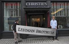 Christie's employees pose for a photograph with a Lehman Brothers sign at Christie's in central London September 24, 2010. REUTERS/Andrew Winning