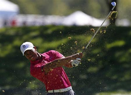 Tiger Woods of the U.S. watches his approach shot on the first hole during the third round of the BMW Championship golf tournament at the Conway Farms Golf Club in Lake Forest, Illinois, September 14, 2013. REUTERS/Jim Young