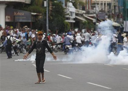 A protester supporting the opposition Cambodia National Rescue Party (CNRP) reacts as police fire tear gas during clashes near the Royal Palace in central Phnom Penh September 15, 2013. REUTERS-Samrang Pring