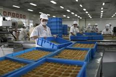 Feshly-baked mooncakes pass along a conveyor belt at a mooncakes factory in Shanghai September 12, 2013. REUTERS/Aly Song