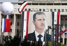 """Российский и китайский государственные флаги рядом с портретом президента Сирии Башара Асада на акции его сторонников в Дамаске 12 октября 2011 года. Правительство Сирии расценивает соглашение, предотвратившее удар США, как """"победу"""", в то время как оппозиция считает, что западные страны таким образом поддерживают их врага в гражданской войне. REUTERS/Khaled al-Hariri"""