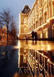 Люди проходят мимо ГУМа дождливым вечером в Москве 26 ноября 2007 года. Рабочая неделя в Москве будет прохладной и пасмурной, ожидают синоптики. REUTERS/Oksana Yushko