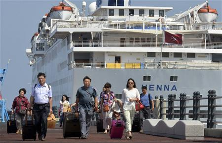 Passengers leave Chinese cruise ship Henna, which is stranded at the port of Jeju on Jeju island, south of Seoul September 15, 2013, to go to an airport to leave Jeju. Picture taken September 15, 2013. Henna, impounded in South Korea over a commercial dispute with another Chinese firm, was due to be released and depart on September 16, 2013, an official at the South Korean port of Jeju told Reuters. REUTERS/Kim Ho-Chun/Yonhap