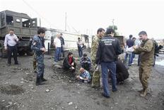 Полицейские и следователи на месте взрыва в селе Серноводск в Чечне 16 сентября 2013 года. Смертник привел в действие взрывное устройство около отделения полиции чеченского села Серноводск, убив троих полицейских. REUTERS/Yelena Fitkulina