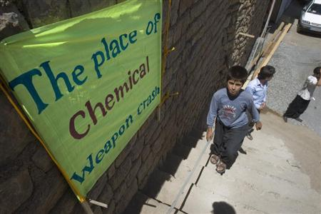 A boy walks past a placard which shows the place of an Iraqi chemical attack during the 1980-1988 war against Iran, in Nowdesheh in Kermanshah province 680 km (425 miles) south west of Tehran in this July 5, 2008 file photo. REUTERS/Morteza Nikoubazl