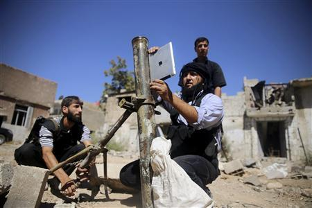 A member of the 'Ansar Dimachk' Brigade, part of the 'Asood Allah' Brigade which operates under the Free Syrian Army, uses an iPad during preparations to fire a homemade mortar at one of the battlefronts in Jobar, Damascus September 15, 2013. REUTERS/ Mohamed Abdullah