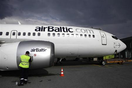 A worker services an airBaltic plane in Riga airport May 13, 2010. REUTERS/Ints Kalnins