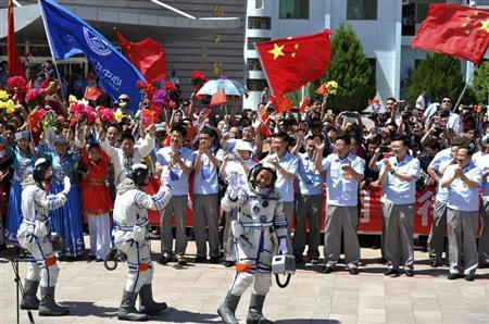 Chinese astronauts (from L to R) Wang Yaping, Zhang Xiaoguang and Nie Haisheng wave before leaving for the Shenzhou-10 manned spacecraft mission at Jiuquan satellite launch center in Jiuquan, Gansu province June 11, 2013. The Shenzhou-10 manned spacecraft will be launched at the Jiuquan Satellite Launch Center at 5:38 p.m. Beijing Time (0938 GMT) today, Xinhua News Agency reported. REUTERS/China Daily